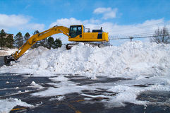 Excavator clearing snow side on Stock Photos