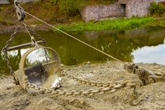 Excavator clears the bottom of the lake from dirt and debris Royalty Free Stock Image