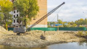 Excavator clears the bottom of the lake from dirt and debris Royalty Free Stock Photo