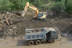 Excavator clears debris from road due to flooding Royalty Free Stock Image