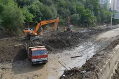 Excavator clears debris from road due to flooding Stock Image