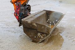 Excavator closeup and wet sand, work pause royalty free stock image