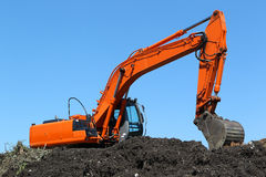 Excavator on a compost heap stock images