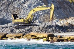 Excavator at construction site. In a sea port Royalty Free Stock Photography