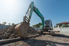 excavator on construction site, digger on gravel heap with shove Stock Images