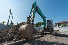 excavator on construction site, digger on gravel heap with shove Royalty Free Stock Photo