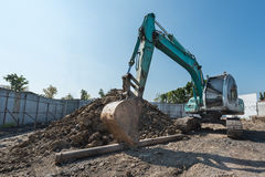 excavator on construction site, digger on gravel heap with shove Stock Photography