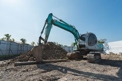 excavator on construction site, digger on gravel heap with shove Royalty Free Stock Photography