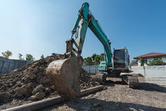 excavator on construction site, digger on gravel heap with shove Stock Image