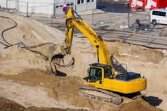 Excavator at construction site during excavation. Excavator on a construction site. excavator bucket with soil, earthworks Stock Photos