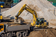 Excavator at construction site during excavation. Excavator on a construction site. excavator bucket with soil, earthworks Royalty Free Stock Photo