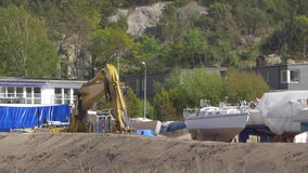 Excavator at Construction Site. GOTHENBURG, SWEDEN - MAY 2015 - An excavator is working at a construction site by a marina with boats on land. Location stock video footage