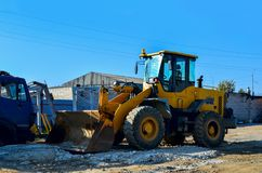 Excavator on the construction site is preparing to load the soil into the dump truck. Wheel loader with iron bucket. Yellow excavator on the construction site is royalty free stock images
