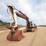 Excavator on construction site. Excavator on road construction site. Wide angle view Royalty Free Stock Photo