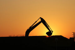 Excavator on construction site silhouette Stock Photos