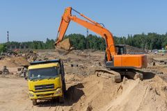 Excavator at the construction site will load the truck with sand stock photo