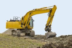 Excavator at a construction site. Yellow excavator at a loamy construction site, partly isolated in light blue back Royalty Free Stock Photos