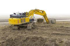Excavator at a construction site. Yellow excavator at a loamy construction site, partly  in white back Royalty Free Stock Images