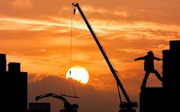 Excavator and crane working sunset background Royalty Free Stock Photo