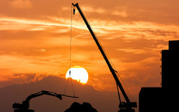 Excavator and crane working sunset background Stock Images