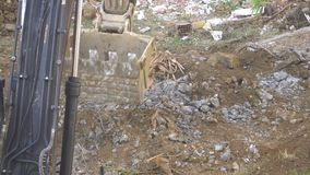Excavator crushes a bucket of rocks next to a dirty ground.  stock footage
