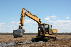 Excavator on cultivated land Stock Image