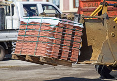 Excavator delivers paving stones. To the road construction Royalty Free Stock Images