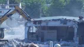 Excavator demolishes building. Excavator is demolishing a building on a construction site stock video footage