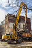 Excavator demolishes old school building Royalty Free Stock Images