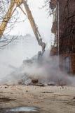 Excavator demolishes old school building Stock Image