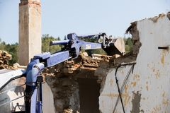 Excavator demolishing a concrete wall. Bulldozer loading demolition debris and concrete waste for recycling at construction site Royalty Free Stock Photos