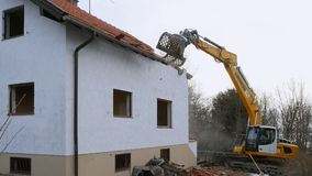 Excavator demolishing a house. Bavaria, Germany, Europe stock footage