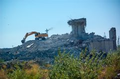 Excavator demolishing an old building, the demolition of the building royalty free stock photo