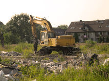 Excavator demolishing remains of building Stock Photo