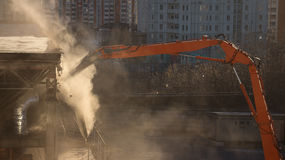 Excavator demolition arm in sunlit dust cloud dismantles the bui. Work of the demolition excavator. Cloud of dust in the sunlight Royalty Free Stock Photos