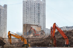 Excavator demolition dismantles the building on background of li. Ving houses. Machinery at construction site behind a fence Royalty Free Stock Photos
