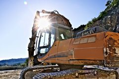 Excavator with demolition hammer in a Carrara marble quarry. stock image