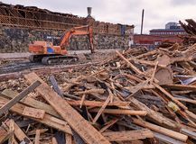 Excavator at demolition site breaking down the building.  Stock Photo