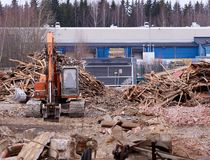Excavator at demolition site breaking down the building.  Stock Image