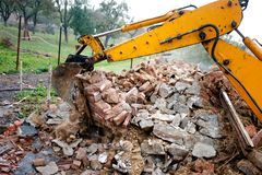 Excavator on demolition site loading bricks Royalty Free Stock Images