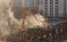 Excavator demolition in sunlit dust cloud dismantles the buildin Royalty Free Stock Images