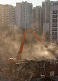 Excavator demolition in sunlit dust cloud dismantles the buildin. Work of the demolition excavator. Cloud of dust in the sunlight Stock Photography