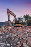 Excavator destroys old building. Excavator standing in the destruction of the old building Royalty Free Stock Photography