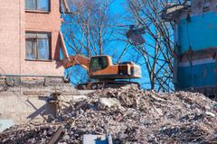 Excavator destroys and ruins the building on a bright sunny day.  Royalty Free Stock Images