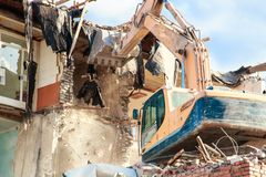 Excavator destroys and ruins the building on a bright sunny day.  Stock Photos