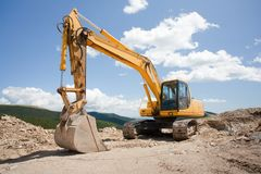 Excavator, digger, earthmover at construction site. Excavator or digger (construction machinery) at a construction site outdoors Stock Images