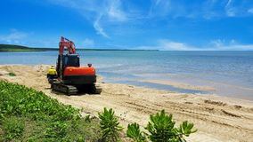 Excavator moving beach sand after erosion. Excavator or digger moving beach sand after erosion by the tides on a tropical beach with calm ocean in Cairns Royalty Free Stock Photos