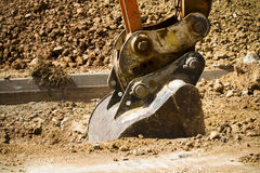 Excavator digging a deep trench Stock Photography