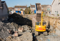 Excavator Digging while Dumper Truck is Unloading. Excavator is digging a house foundation in a residential area while a dumper truck is unloading construction royalty free stock photography