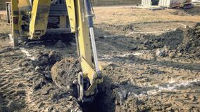 Excavator is digging foundations of house. Excavating of hole. Construction machinery, ground works. Digger works on building. Buc stock video